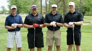 Four male golfers smile at the camera, standing in a row with their hands crossed on their clubs.